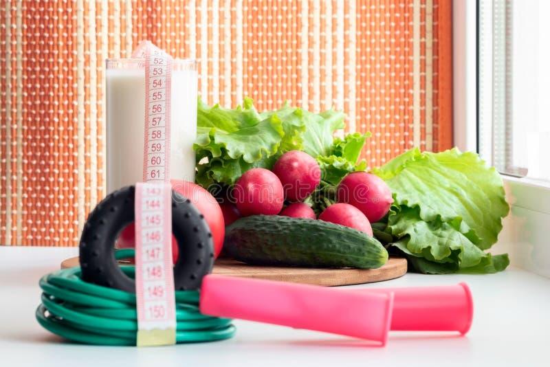 Gymnastiek- springtouw en groenten voor een gezonde voeding - de tomaat, de komkommer, de radijs en de sla zijn op de lijst dicht stock foto