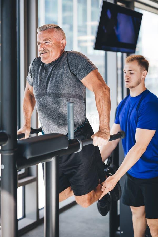 Gymnastiekinstructeur die de hogere mens helpen bij de gymnastiek royalty-vrije stock afbeeldingen