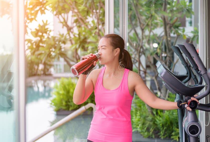 Gymnastiekvrouw die drinkwater uitwerken op geschiktheidscentrum royalty-vrije stock foto's