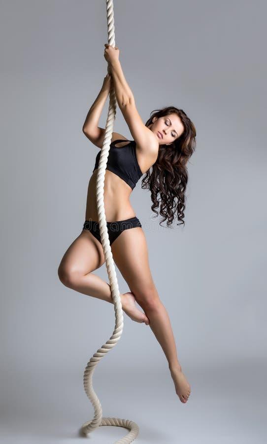 gymnastik Sexig brunettutbildning på rep royaltyfria bilder