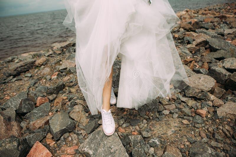 Gymnastikskor för brudstilklänning sätter på land våta stenar arkivfoto