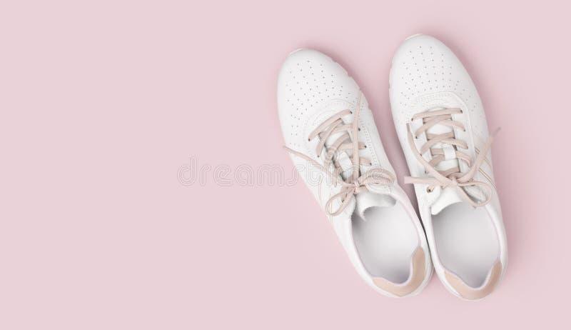 Gymnastikskor för vitt läder med snör åt isolerat på rosa bakgrund arkivfoton