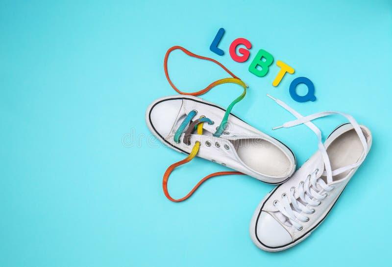 Gymnastikskor med färgrika skosnöre och förkortning LGBTQ på färgbakgrund royaltyfri bild