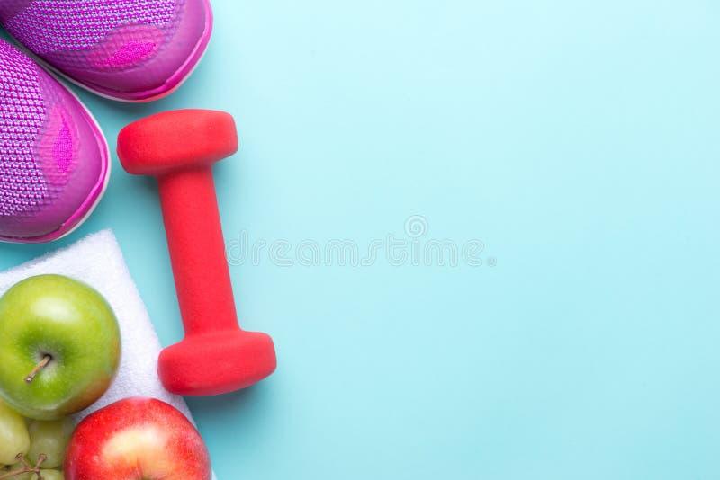Gymnastikskor och hantelkondition på en grå bakgrund Olika hjälpmedel för sport Sportskor och vatten med uppsättningen för sporta royaltyfri fotografi