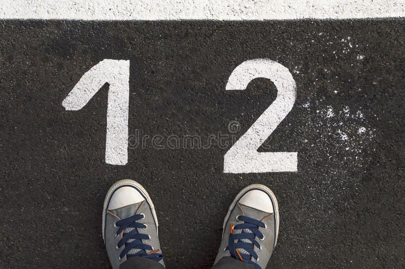 Gymnastikskor på asfaltvägen med nummer 1 och 2 royaltyfria foton