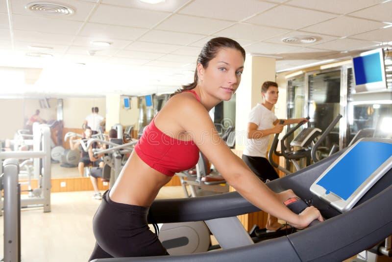 Gymnastiktretmühle, die Innenraum der jungen Frau laufen lässt stockbilder