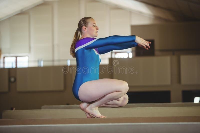 Gymnastique de pratique de gymnaste féminin sur le faisceau d'équilibre photographie stock libre de droits