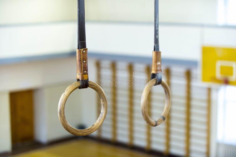 Gymnastisk cirkel som hänger i idrottshall Sund livsstil och konditionbegrepp arkivbild
