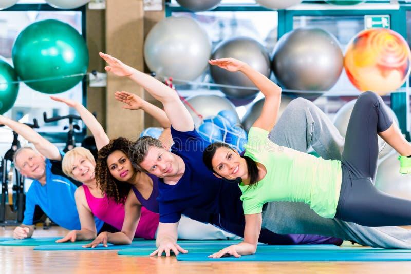 Gymnastisk grupp i idrottshall som övar och utbildar arkivfoto
