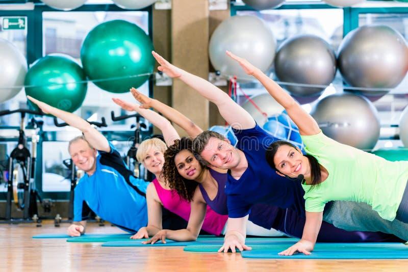 Gymnastisk grupp i idrottshall som övar och utbildar arkivbilder
