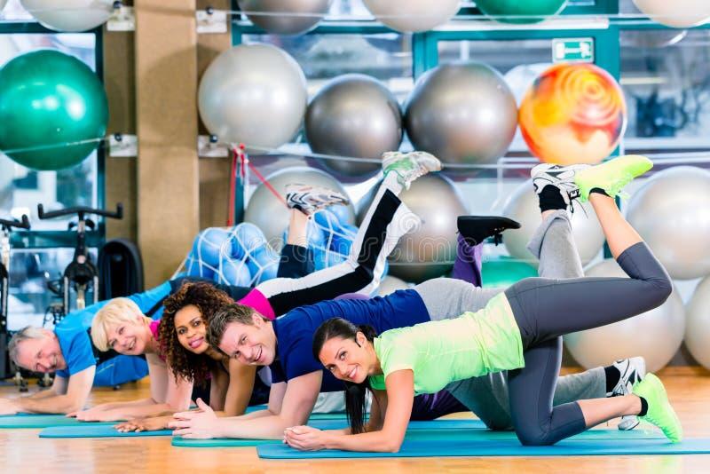 Gymnastisk grupp i idrottshall som övar och utbildar arkivbild