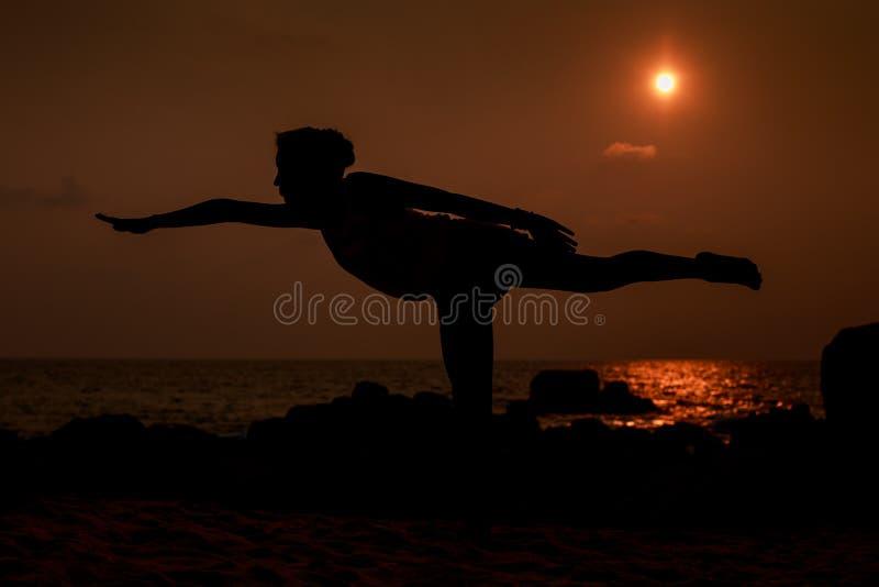 gymnastkonturn poserar in benskalan mot solskiva över havet royaltyfria bilder