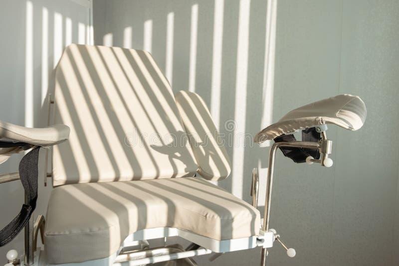 Gynäkologischer Stuhl Morgenlichtstreifen durch die Vorhänge Ärztlicher Dienst für Prüfung von Frauen im Krankenhaus stockfoto
