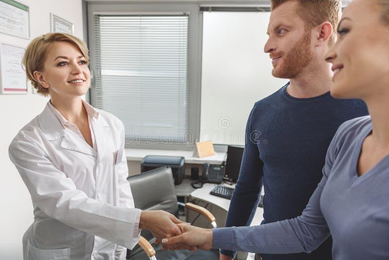 Gynécologue bienveillant serrant la main au patient photographie stock