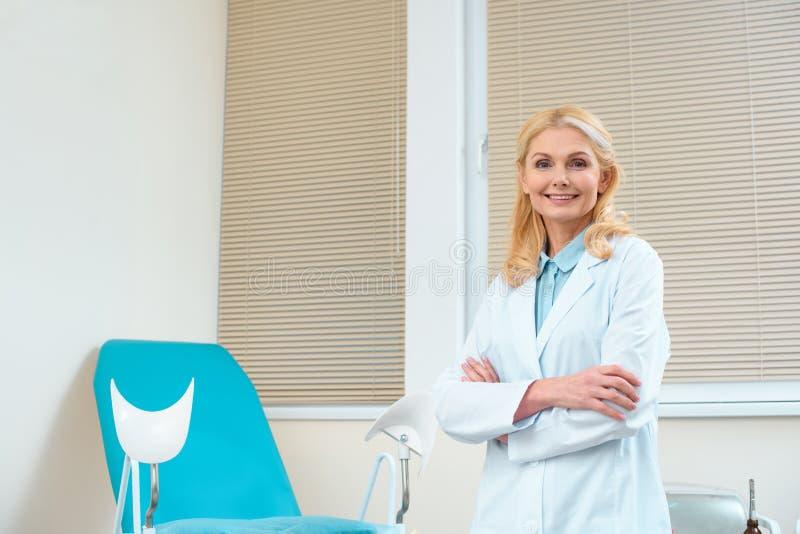 gynécologue féminin de sourire avec les bras croisés devant images stock