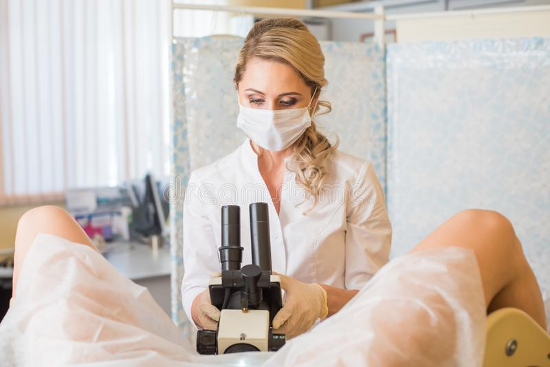 Gynécologue professionnel examinant son patient féminin sur une chaise gynécologique photos libres de droits