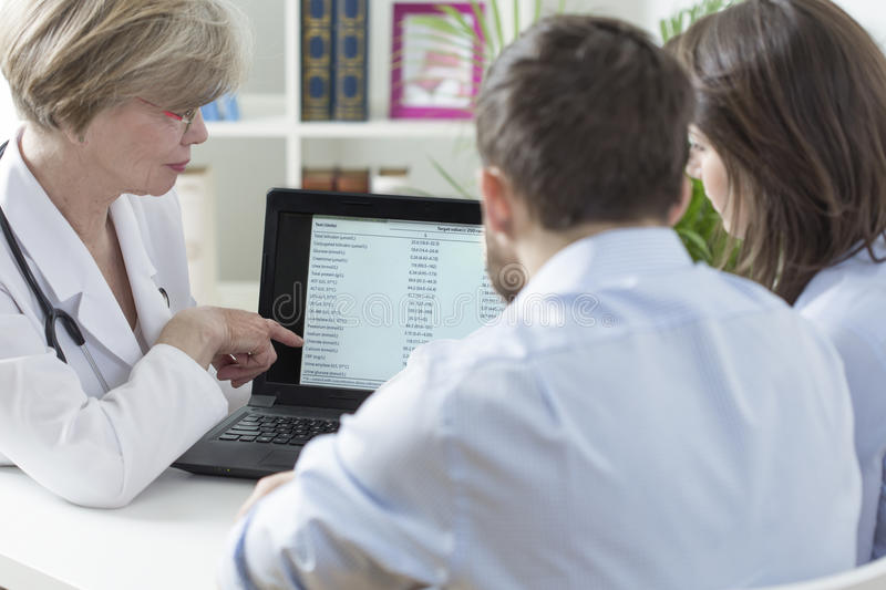 Gynecologist analyzing tests results. Female gynecologist analyzing with couple tests results stock photos