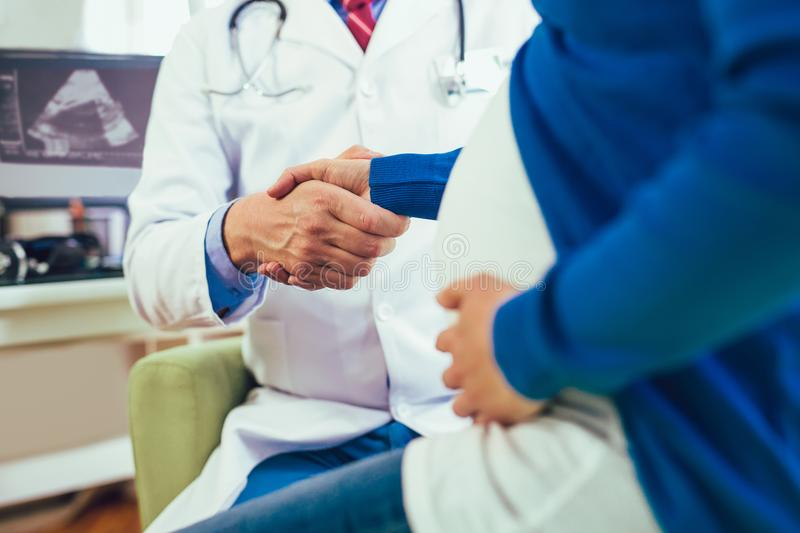 Gynecologist doctor and pregnant woman meeting at hospital. Gynecologist doctor and pregnant woman meeting at doctors office royalty free stock photo