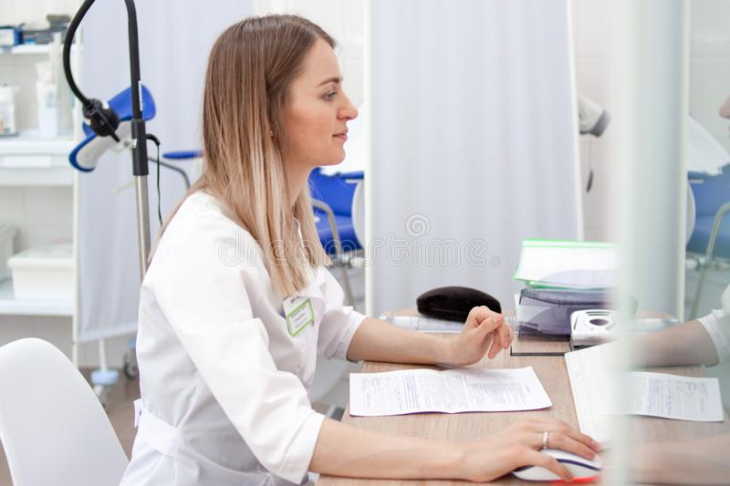 Gynecologist doctor in white uniform in clinic hospital works on computer. Gynecological cabinet with chair and other royalty free stock photos