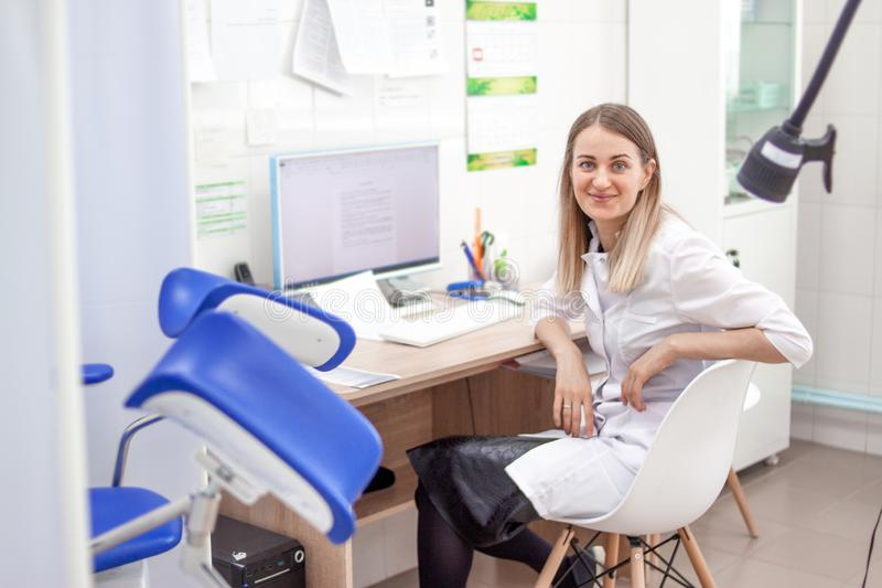 Gynecologist doctor in white uniform in clinic hospital works on computer. Gynecological cabinet with chair and other stock photos
