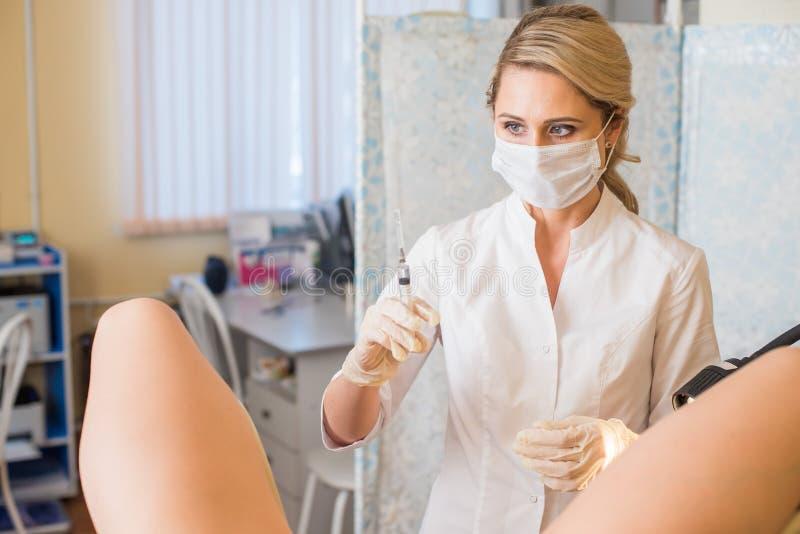 Gynekologen gör en injektion Den attraktiva doktorsgynekologen behandlar patienten royaltyfri foto