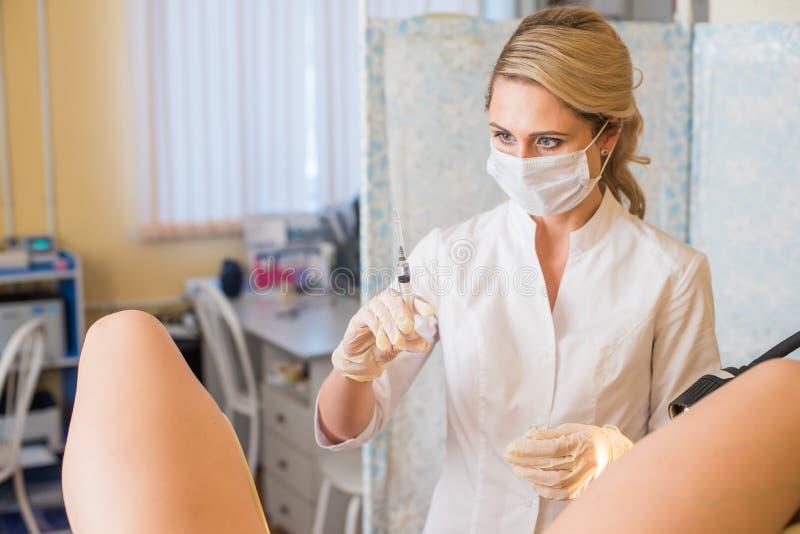 Gynekologen gör en injektion Den attraktiva doktorsgynekologen behandlar patienten fotografering för bildbyråer