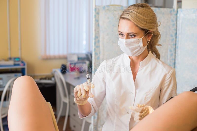 Gynekologen gör en injektion Den attraktiva doktorsgynekologen behandlar patienten royaltyfri bild