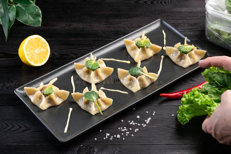 Gyoza με το σπανάκι, το ricotta και το αρνί σε ένα μαύρο πιάτο σε ένα σκοτεινό ξύλινο υπόβαθρο στοκ εικόνες με δικαίωμα ελεύθερης χρήσης