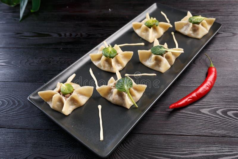 Gyoza με το σπανάκι, το ricotta και το αρνί σε ένα μαύρο πιάτο σε ένα σκοτεινό ξύλινο υπόβαθρο στοκ φωτογραφίες