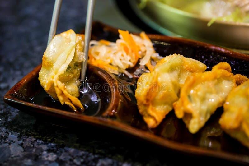 Gyoza auf Essstäbchen Selbst gemachter Asiat Vegeterian Potstickers mit Sojasoße und Schweinefleisch Japanische Mehlklöße mit Ess stockfotos