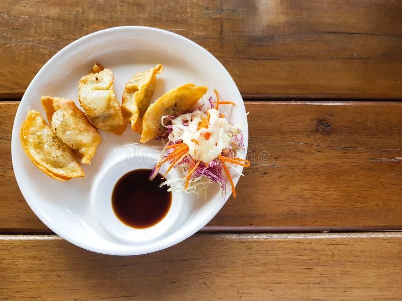 Gyoza sur le plat blanc avec la sauce de soja et le côté avec le dessus de salade du mA photos libres de droits