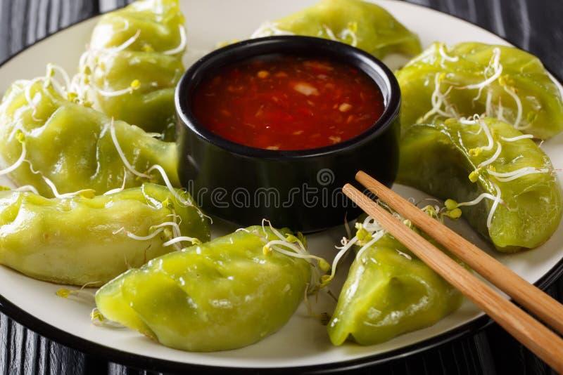 Gyoza verde das bolinhas de massa do alimento japonês saudável com o matcha com molho e para microgreen o close-up em uma placa h fotografia de stock