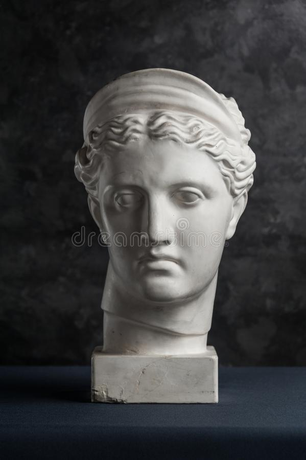 Gypsum copy of ancient statue Diana head on a dark textured background. Plaster sculpture woman face. royalty free stock photo