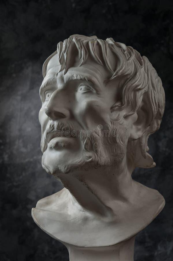 Gypsum copy of ancient statue Seneca head on dark textured background. Plaster sculpture man face. White gypsum copy of ancient statue of Lucius Seneca head for stock photography
