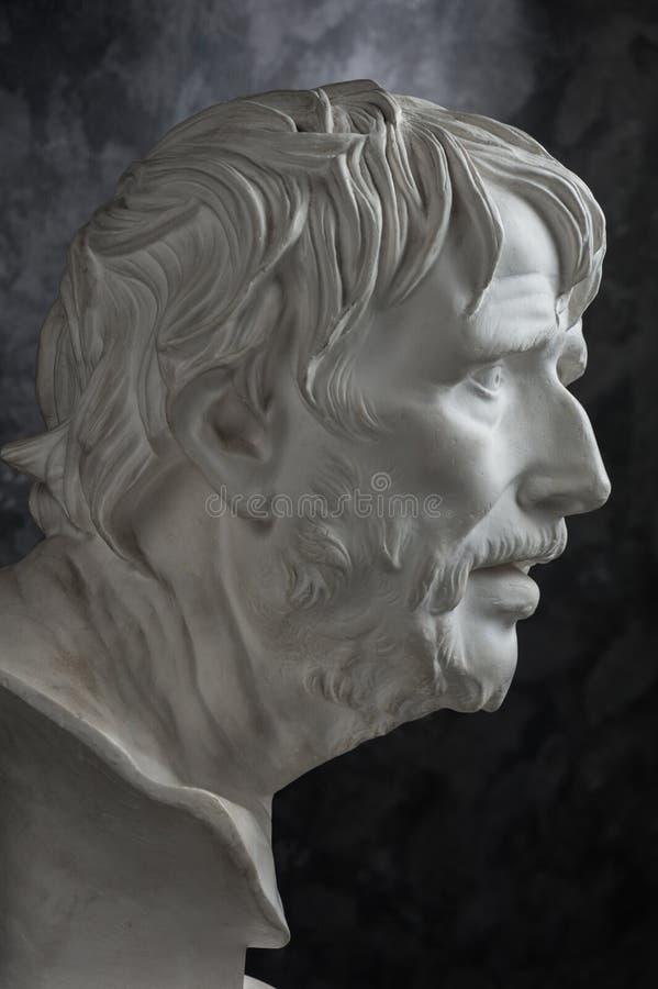 Gypsum copy of ancient statue Seneca head on dark textured background. Plaster sculpture man face. White gypsum copy of ancient statue of Lucius Seneca head for royalty free stock image