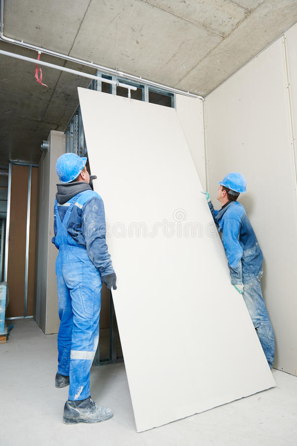 Gypsum plaster board walling installation. Gypsum plasterboard installation during indoor walling by workers royalty free stock image