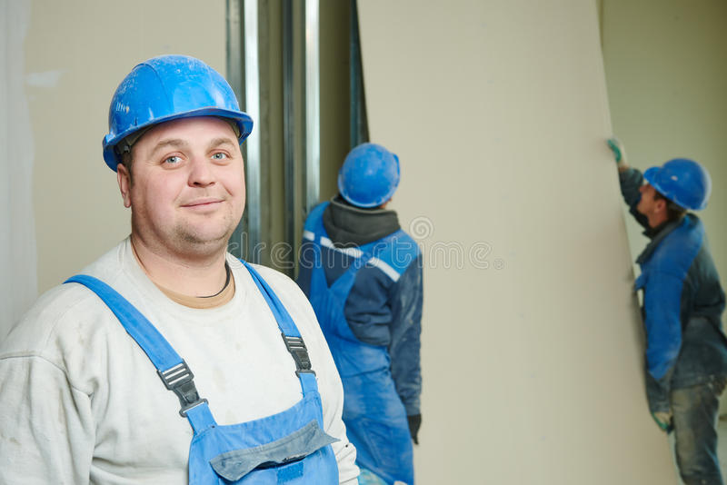 Gypsum plaster board walling installation. Portrait of builder in front of gypsum plasterboard installation during indoor walling by workers stock photos