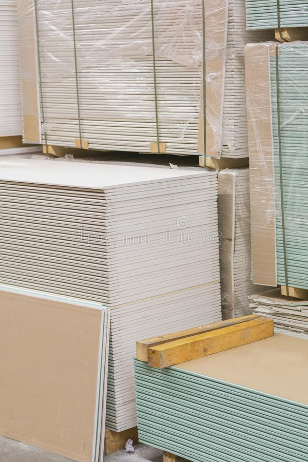 Gypsum plasterboard in the pack. The stack of gypsum board preparing for construction. Pallet with plasterboard in the building. Store. Construction Materials stock photo
