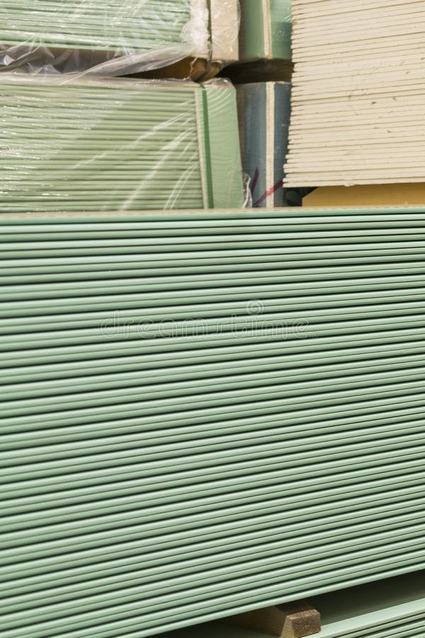 Gypsum plasterboard in the pack. The stack of gypsum board preparing for construction. Pallet with plasterboard in the building. Store. Construction Materials stock images