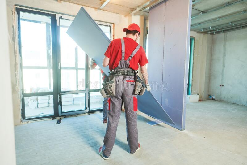 Gypsum plasterboard work. Drywall construction at home. Contractor worker installing wall royalty free stock photography