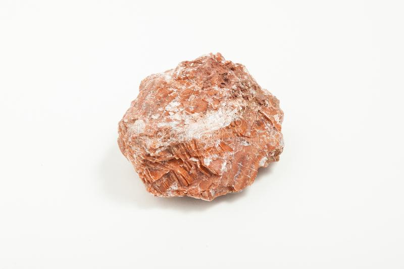 Ore red gypsum on white background. Gypsum is a soft sulfate mineral composed of calcium sulfate dihydrate, It is widely mined and is used as a fertilizer, and stock images