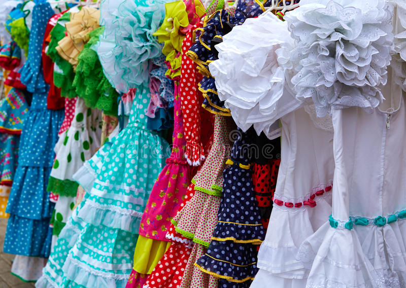 Gypsy dresses in an andalusian Spain market. Gypsy dresses hanging in a row in an andalusian Spain outdoor market royalty free stock image