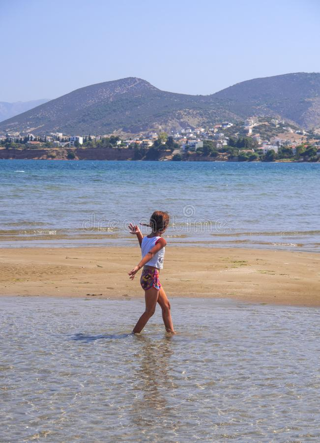 Gypsy Girl running on the sand of Liani Ammos beach on a Sunny summer day. Chalkida, Evia Island royalty free stock photos