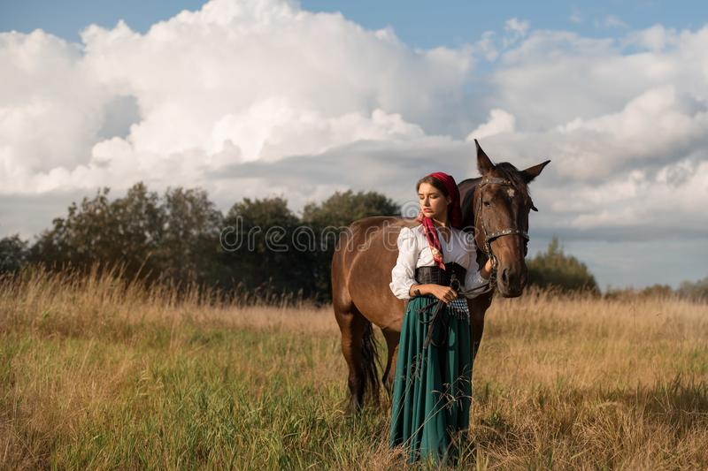 Gypsy with a horse in the field in summer. Beautiful gypsy with a horse in the field in summer stock photo
