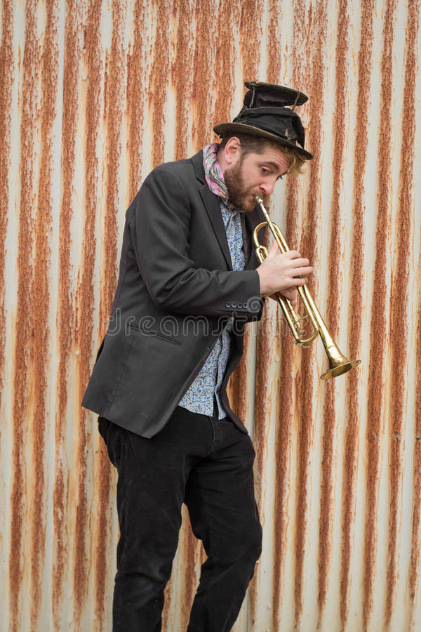 Gypsy Trumpet Musician. Stylish bearded gypsy plays trumpet by rusty fence royalty free stock photos
