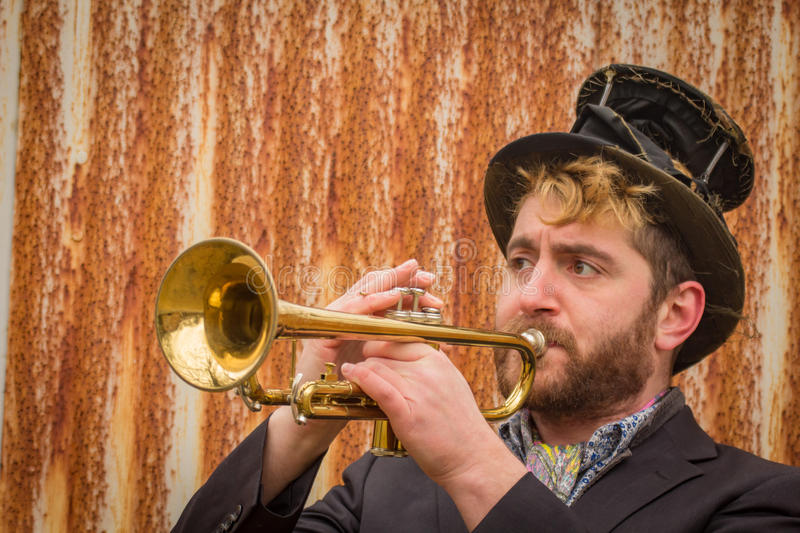 Gypsy Trumpet Musician. Stylish bearded gypsy plays trumpet by rusty fence stock photography