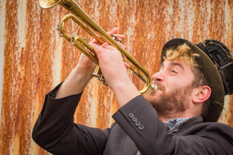 Gypsy Trumpet Musician. Stylish bearded gypsy plays trumpet by rusty fence stock images