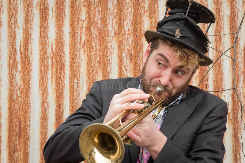 Gypsy Trumpet Musician. Stylish bearded gypsy plays trumpet by rusty fence royalty free stock photo