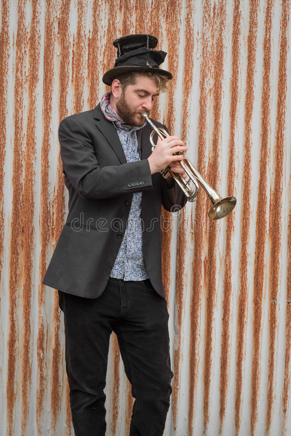 Gypsy Trumpet Musician. Stylish bearded gypsy plays trumpet by rusty fence stock photo