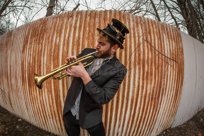 Gypsy Trumpet Musician. Stylish bearded gypsy plays trumpet by rusty fence royalty free stock image